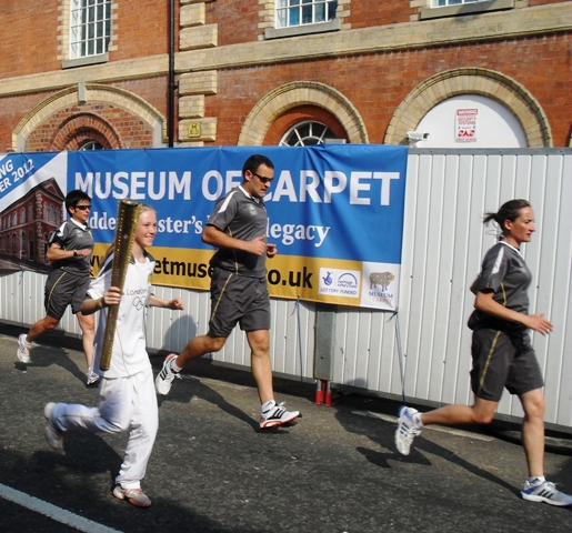 The Olympic torch is carried past the Museum of Carpet, 24 May 2012