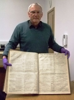 A research volunteer shows off a bound copy of the Kidderminster Shuttle form the early 20th century